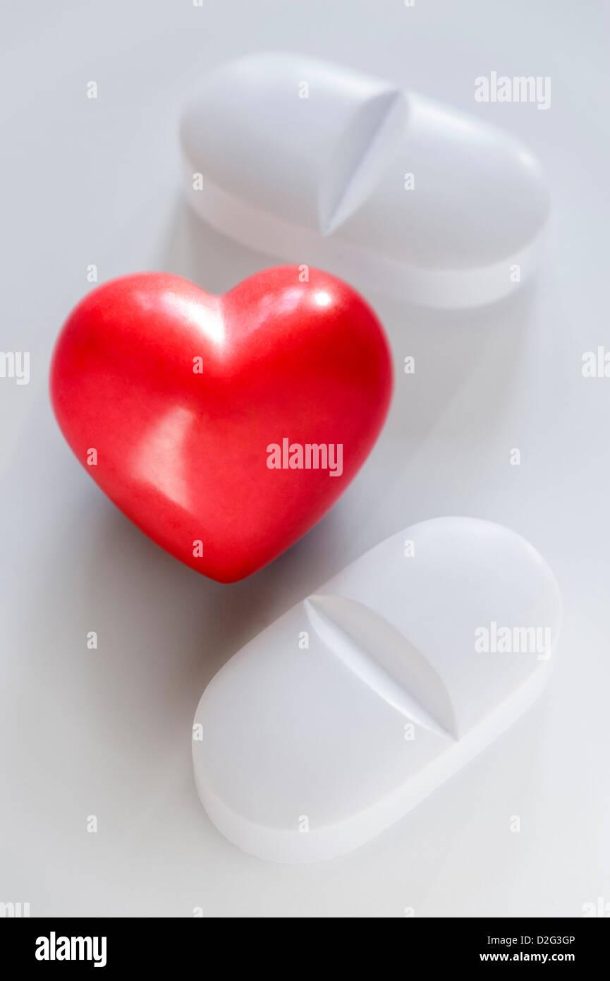 Deux pilules blanches et un cœur rouge sur fond blanc Photo Stock
