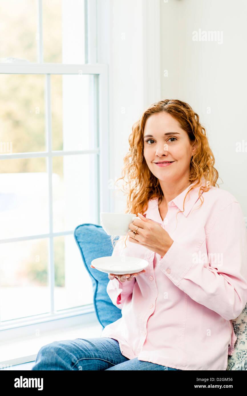 Smiling caucasian woman relaxing on couch holding fenêtre par tasse de café Banque D'Images