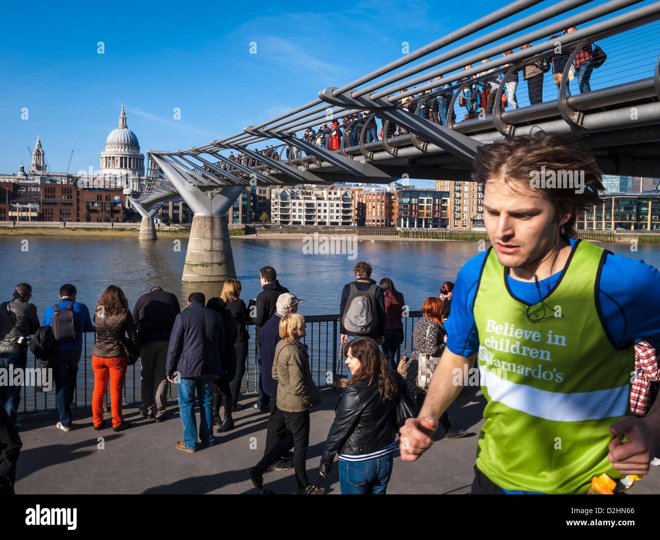 Un jeune homme qui court sous millenium bridge in a sunny day Banque D'Images