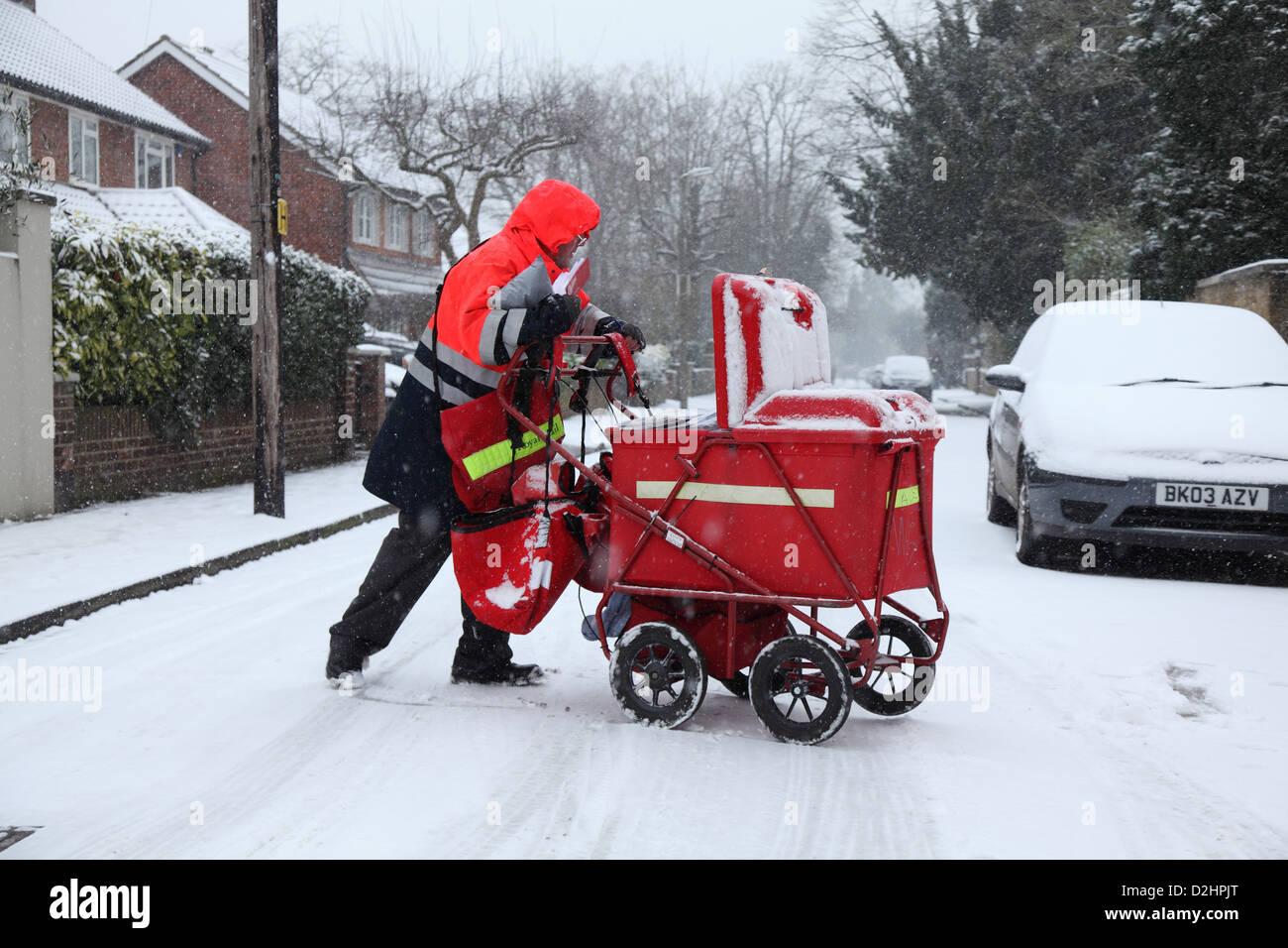 Facteur distribue le courrier dans une chute de neige. Banque D'Images