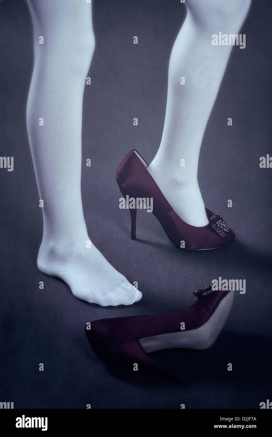 Une fille en bas blancs avec des chaussures trop grande Photo Stock