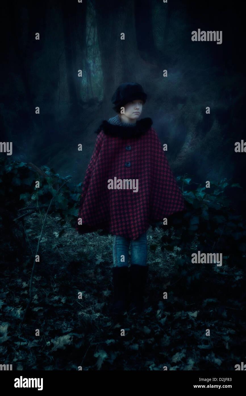 Une fille avec une cape rouge dans les bois sombres Photo Stock