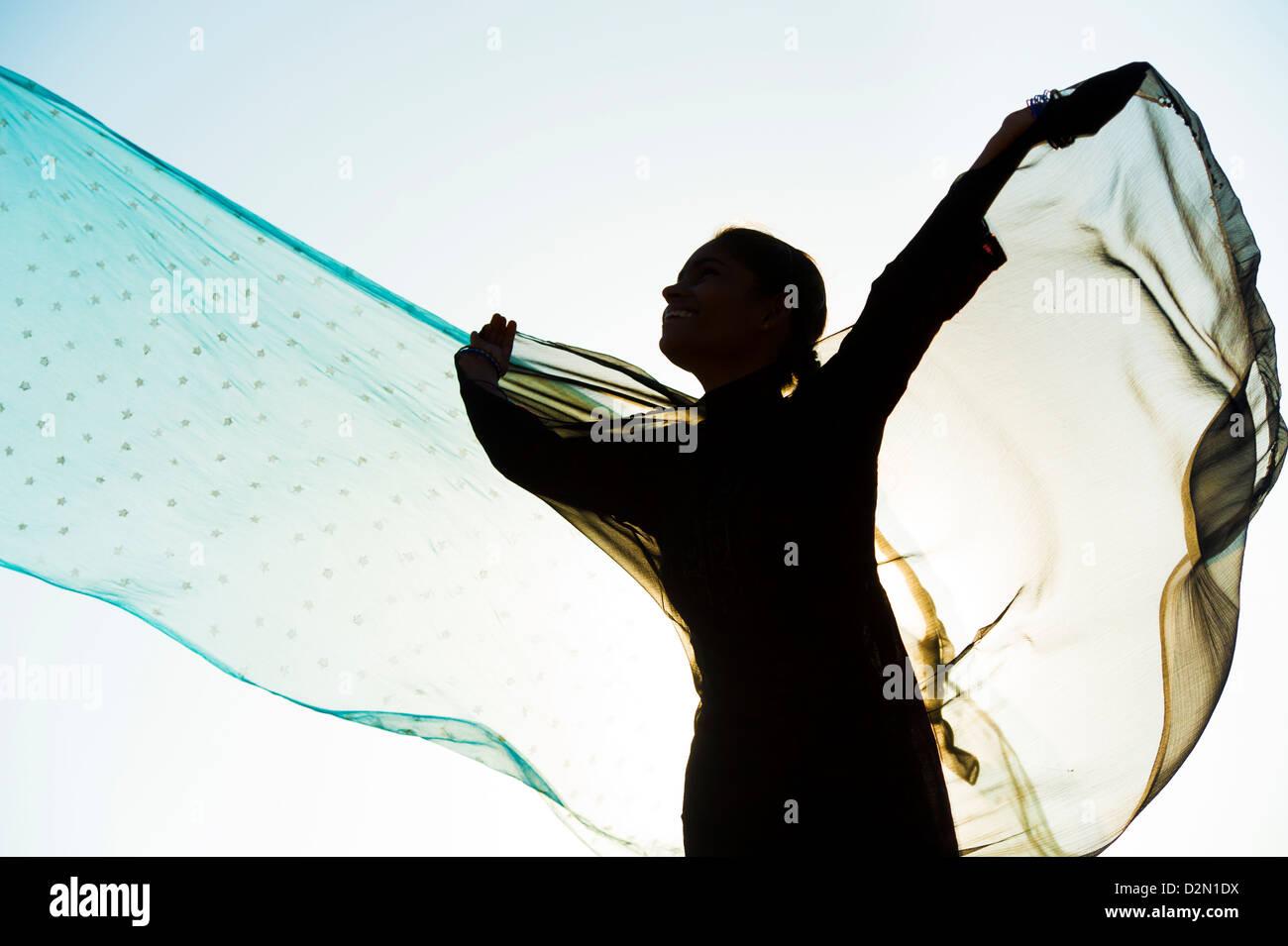 Fille indienne avec des voiles dans le vent tourne vers le soleil. Silhouette. L'Inde Photo Stock