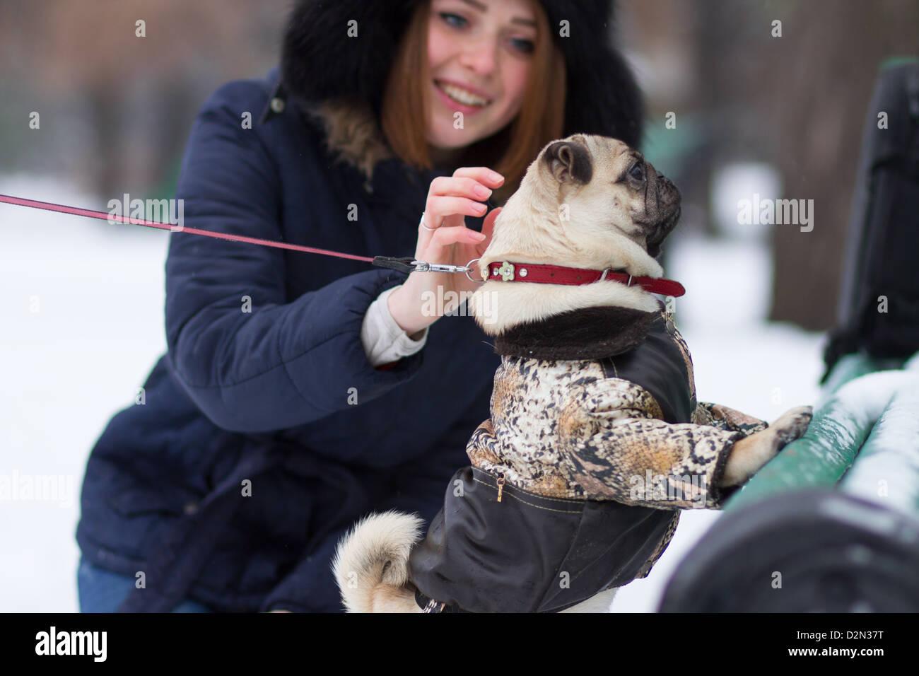 Adolescent aux cheveux rouge fille jouant avec drôle chiot pug sur la neige dans le parc Photo Stock