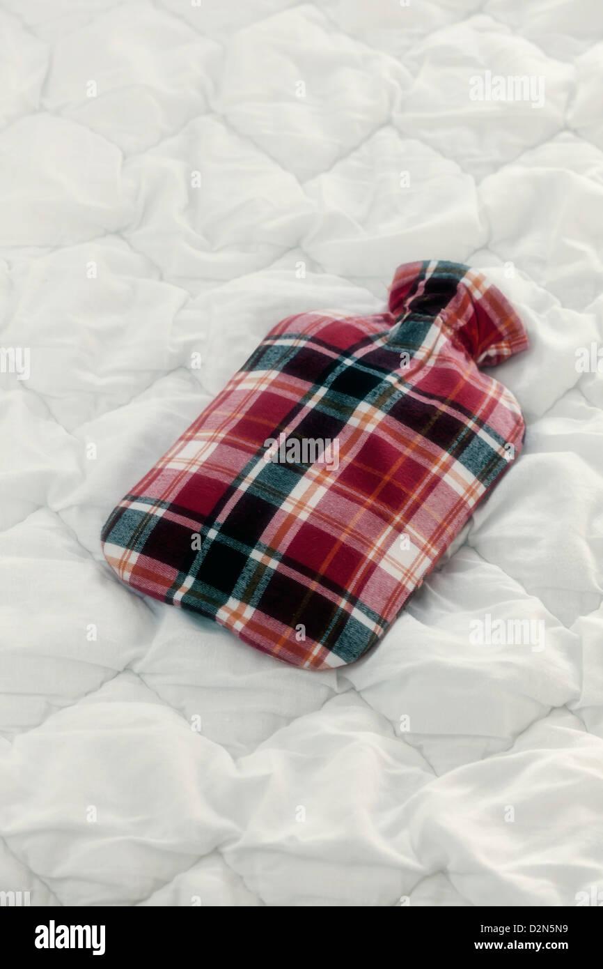 Une bouteille d'eau chaude vintage sur une couette Banque D'Images