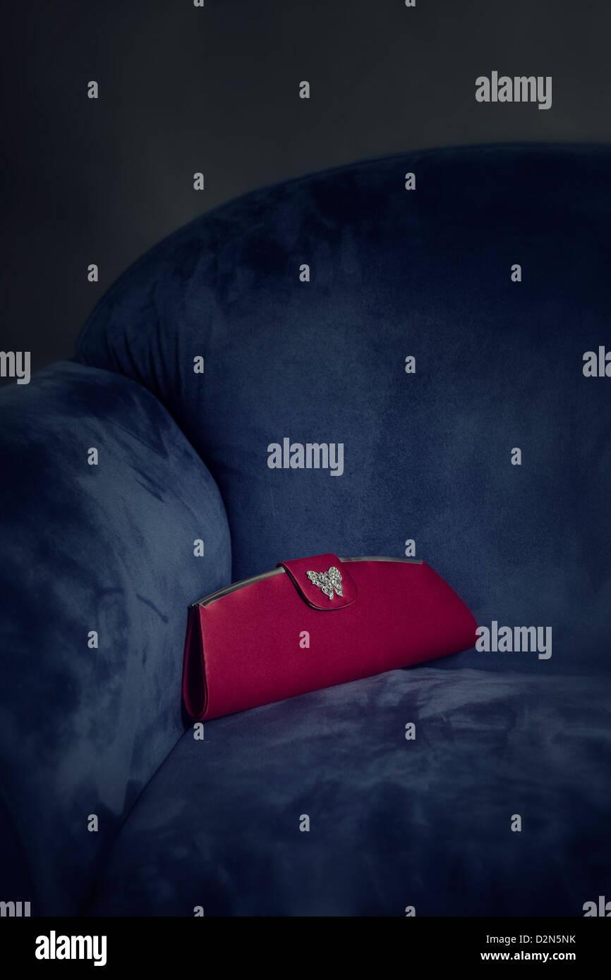 Un sac à main rouge couché sur un fauteuil bleu Photo Stock