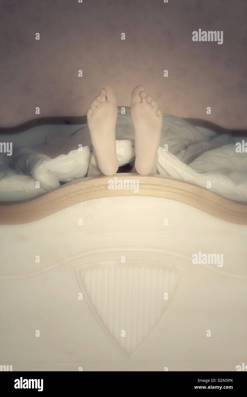 Les pieds dans un lit Photo Stock