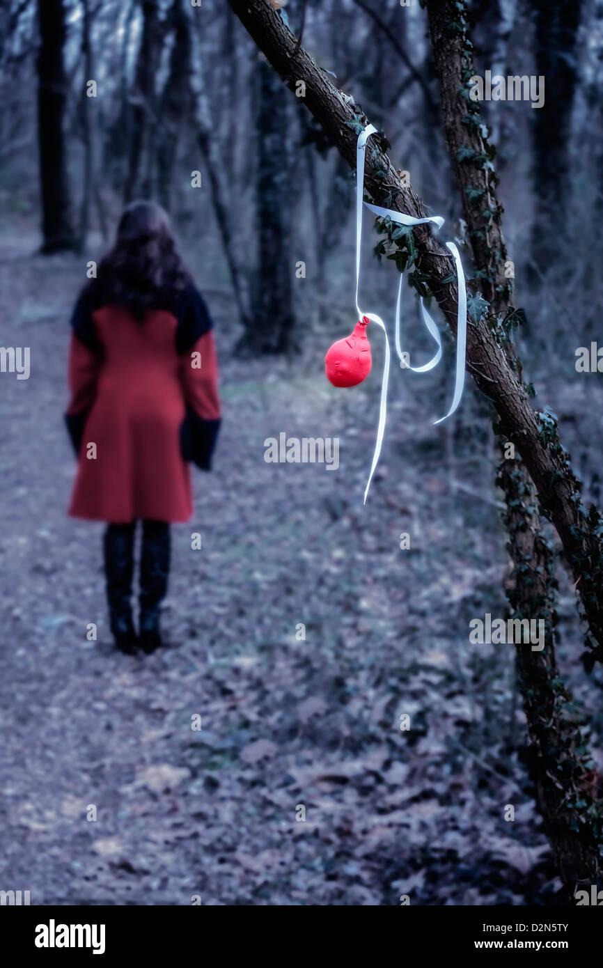 Un vieux ballon rouge suspendu à une branche, à une distance d'une femme dans un manteau rouge Photo Stock