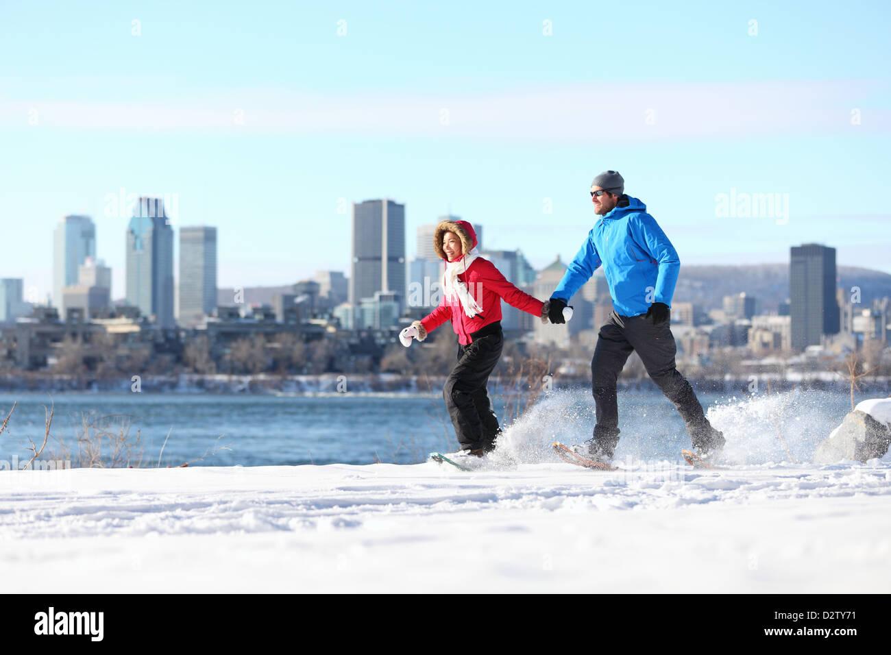 Heureux couple raquette à Montréal avec des toits de la ville et la rivière st. Lawrence en arrière Photo Stock