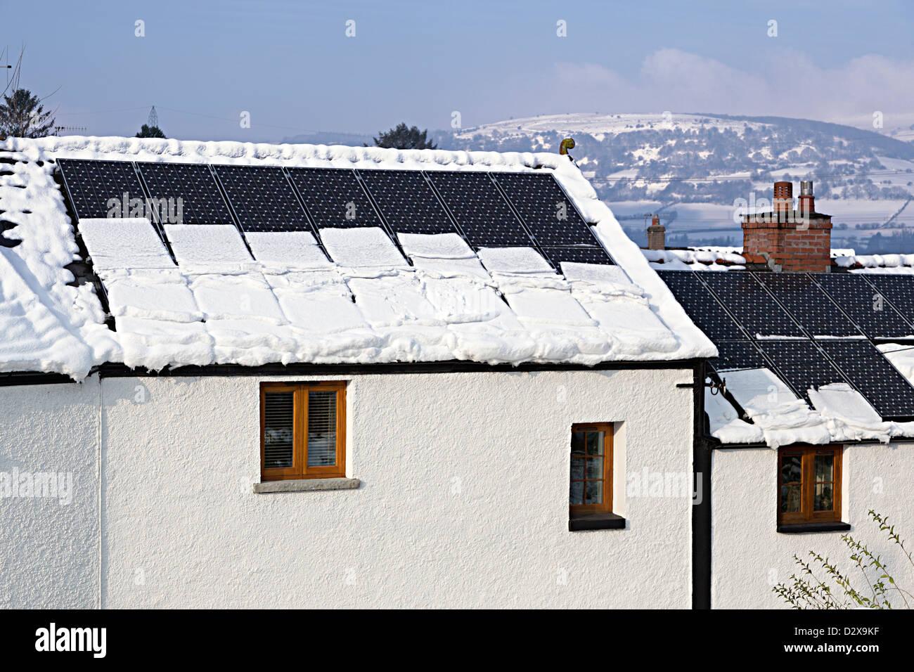 La neige glisse de panneaux PV solaire et mettre du poids sur les gouttières de la maison, Llanfoist, Pays Photo Stock