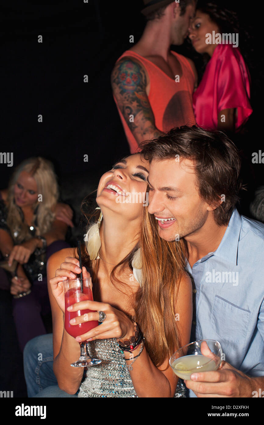 Laughing couple hugging and drinking cocktails in nightclub Banque D'Images