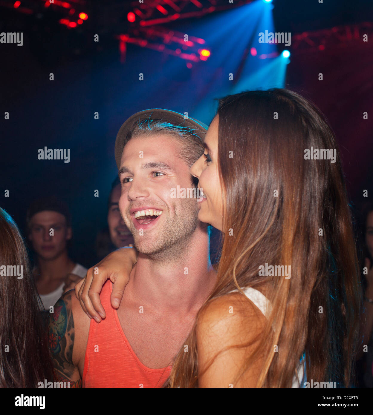 Smiling couple hugging in nightclub Banque D'Images