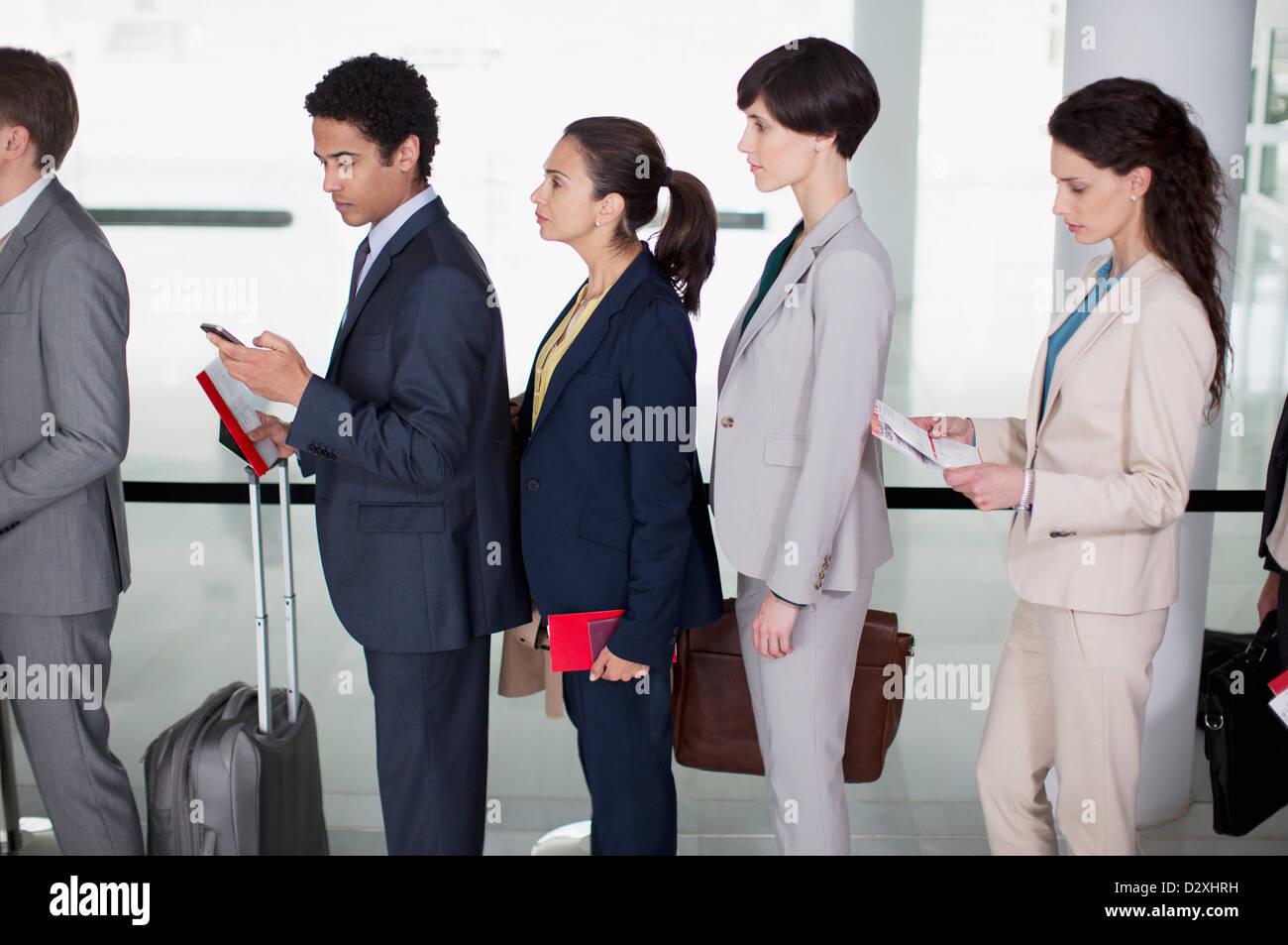 Les gens d'affaires à l'aéroport dans la file d'attente permanent Photo Stock