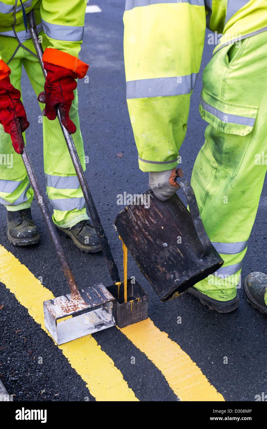 Les travailleurs de la route double peinture lignes jaunes le marquage routier sur une route, UK Photo Stock
