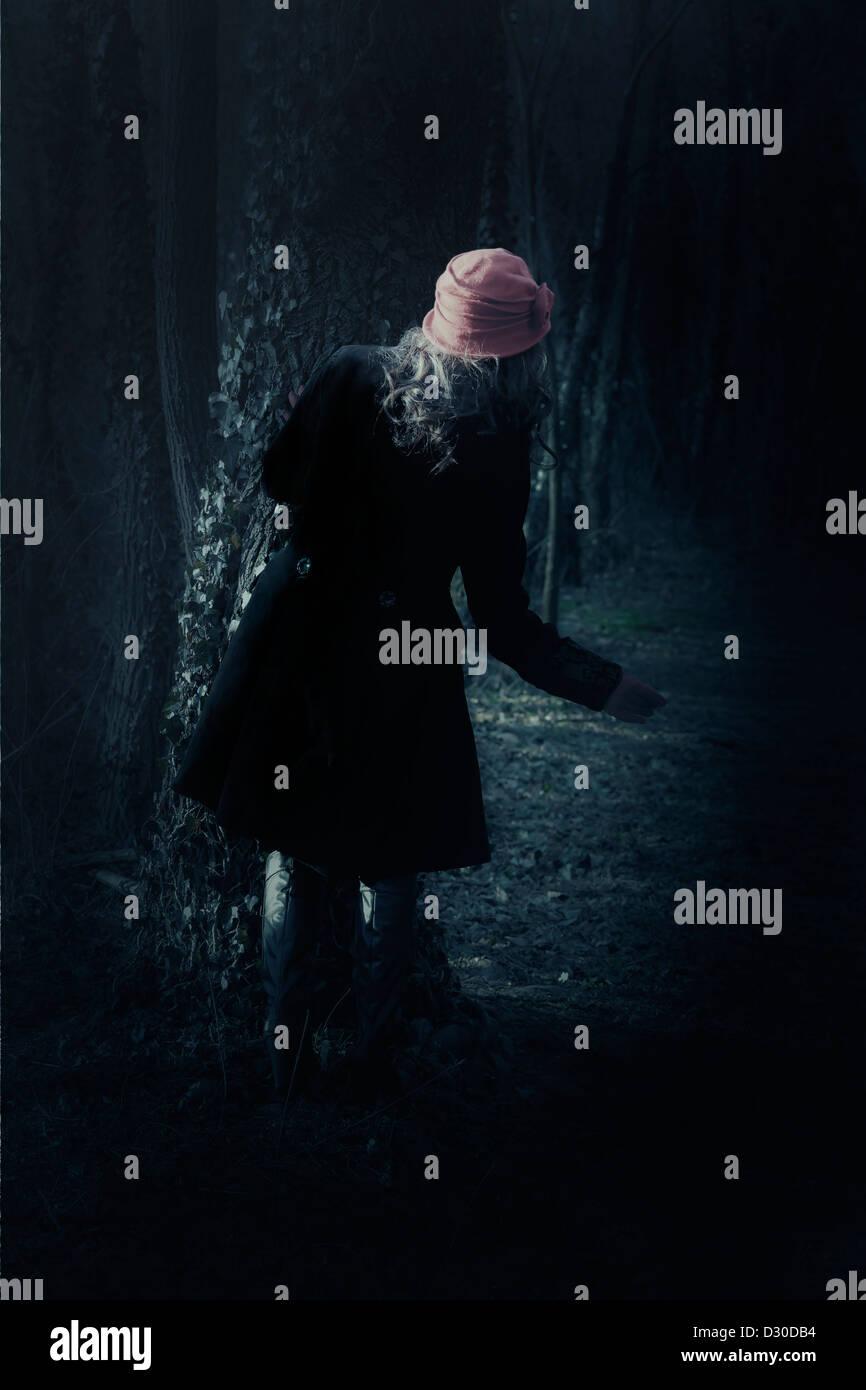 Une femme avec un manteau noir se tient debout derrière un arbre Photo Stock