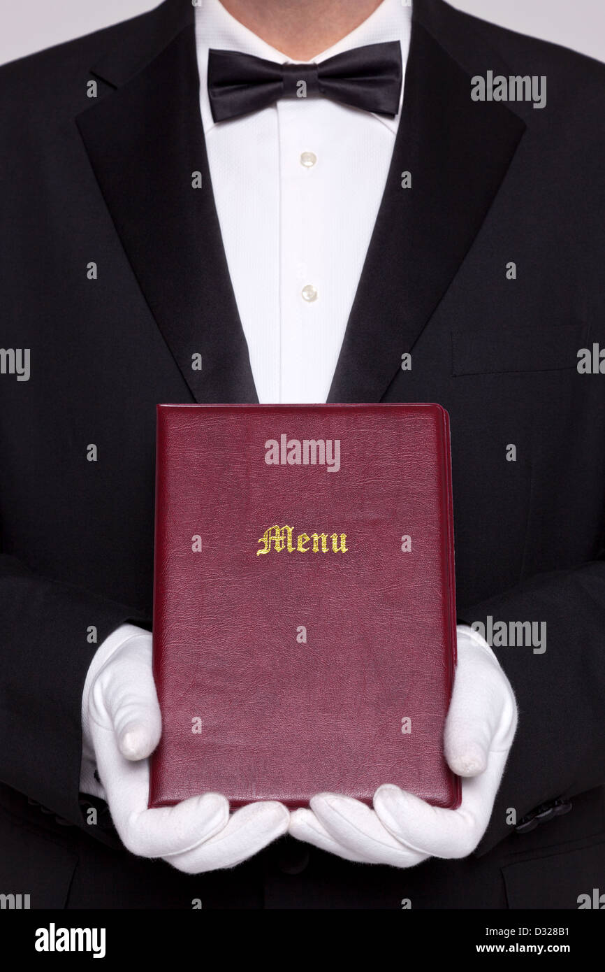 Waiter holding un dossier Menu dans un restaurant. Photo Stock