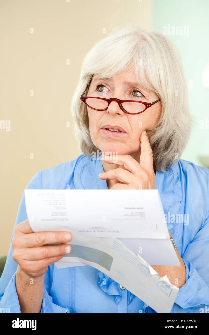 Dame âgée lisant une lettre officielle Photo Stock