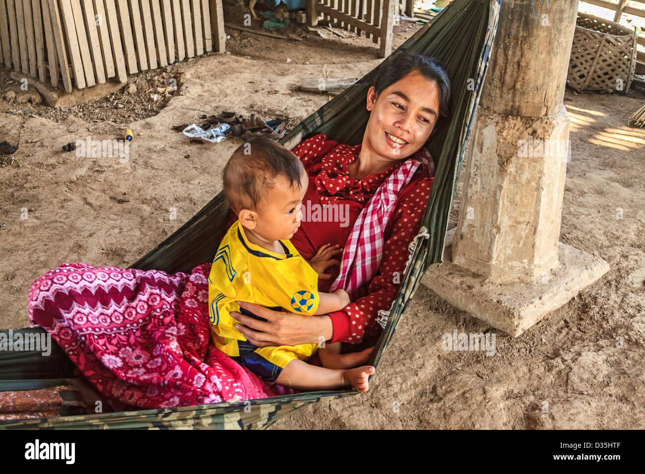 Jeune mère et son fils dans un hamac en Cham village le long du Mékong au sud de Kratie, au Cambodge. Photo Stock