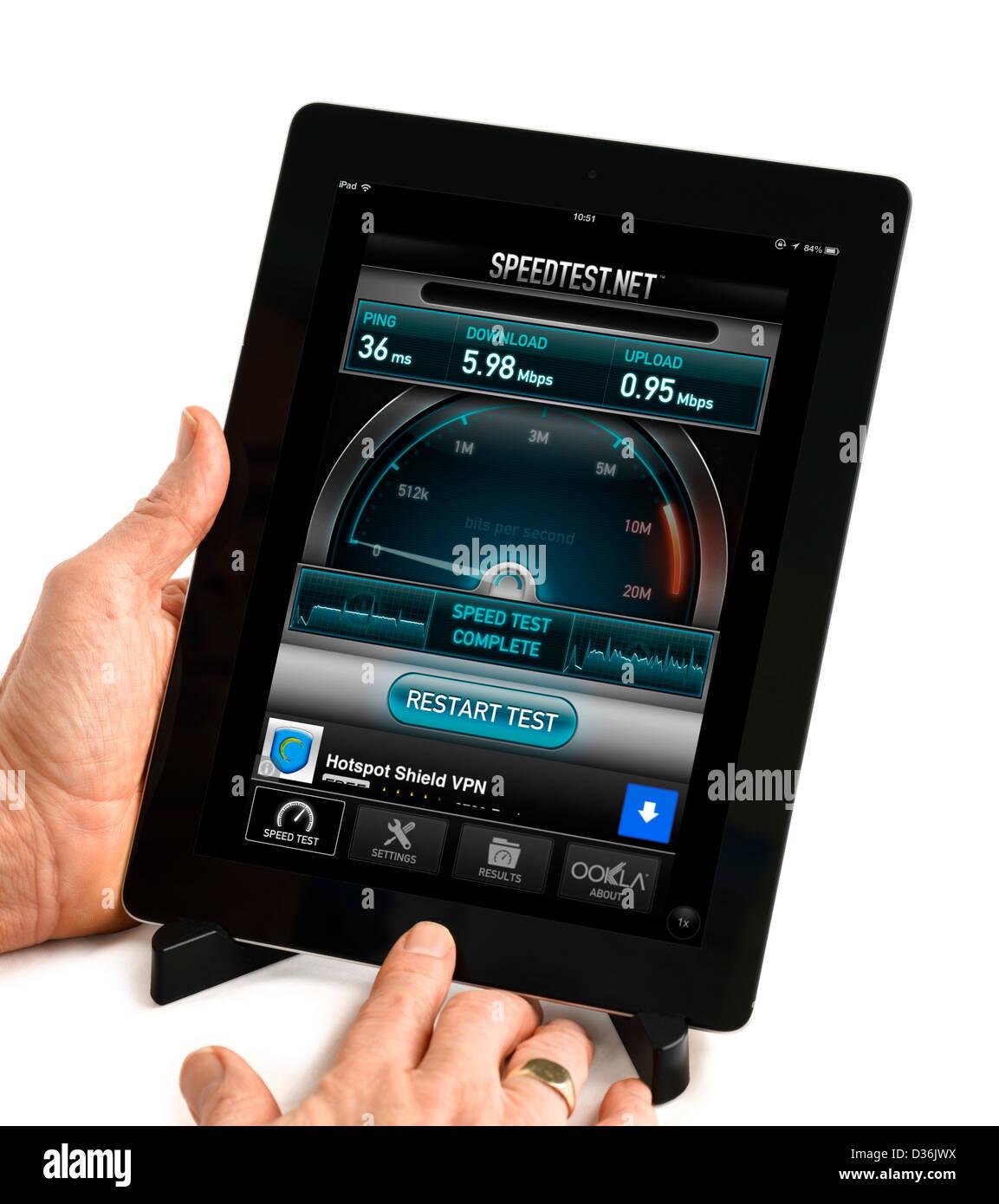 En utilisant le test de vitesse à large bande Speedtest.net app sur un Apple iPad 4e génération Photo Stock