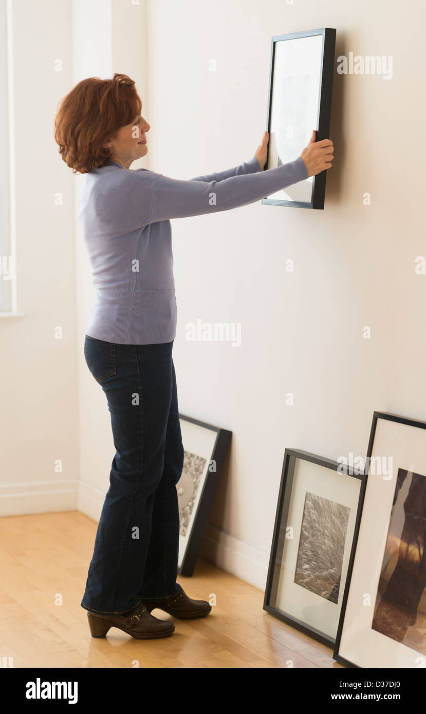 USA, New Jersey, Jersey City, Woman Hanging cadre sur le mur Photo Stock