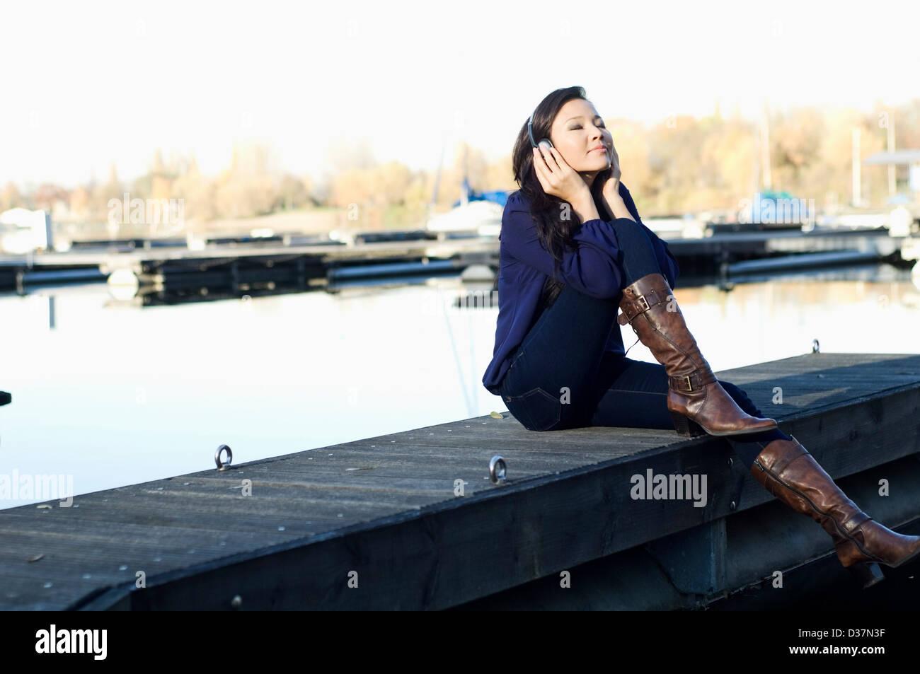 Woman listening to headphones sur le pont Banque D'Images