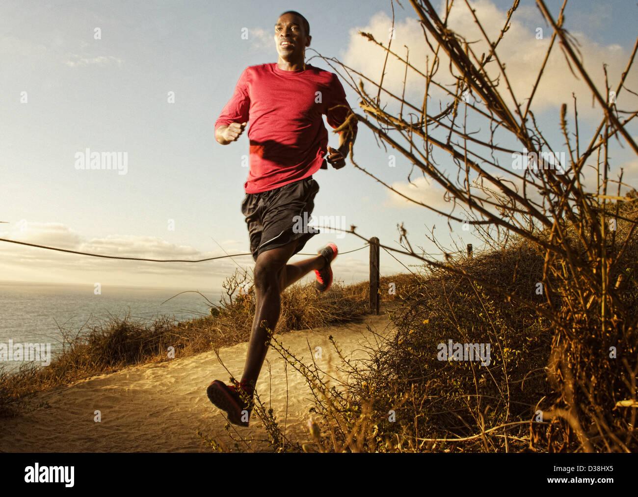 Man running on dirt path Photo Stock