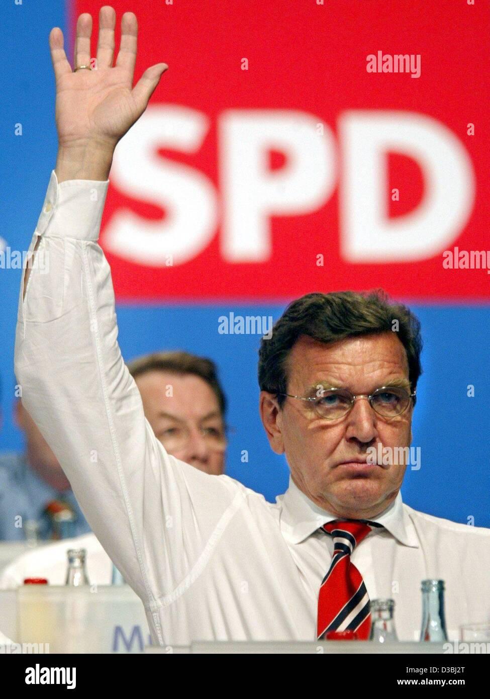 (Afp) - Le Chancelier allemand Gerhard Schroeder lève la main pendant une acclamation lors d'une conférence Photo Stock