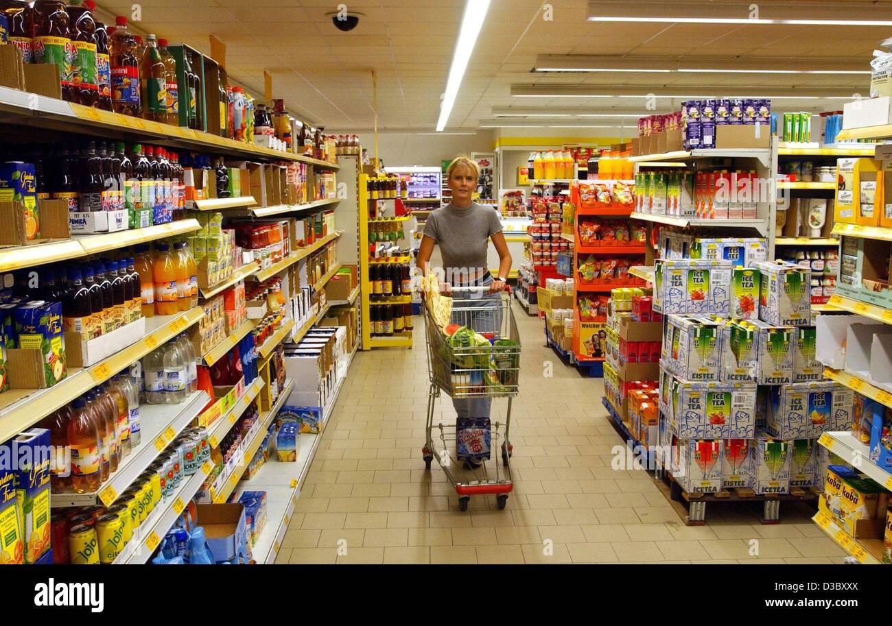 (Afp) - une femme pousse son panier grâce à un supermarché de Berlin, 19 juin 2003. Banque D'Images