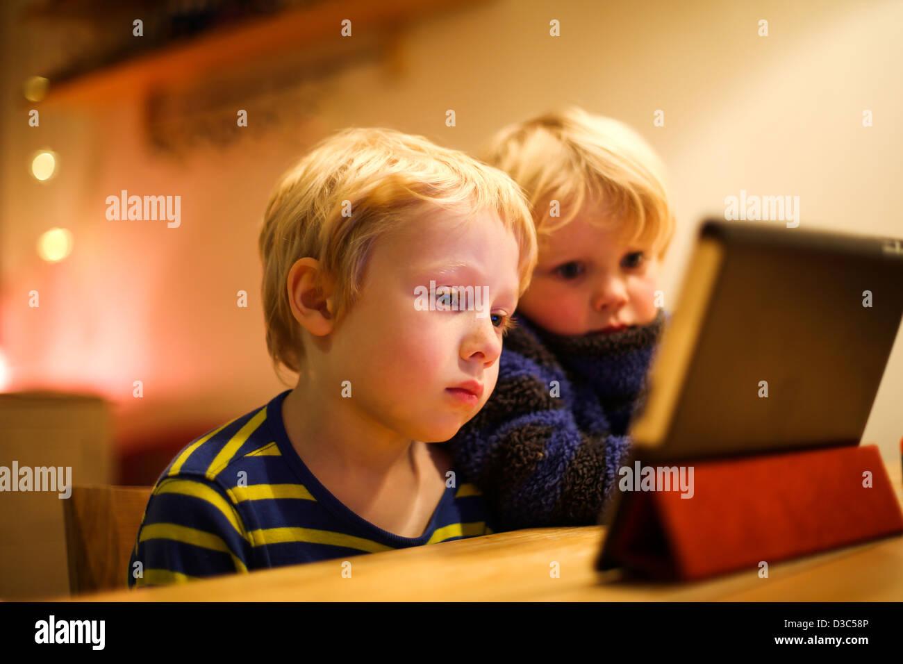Deux jeunes garçons de regarder un film sur un iPad Photo Stock