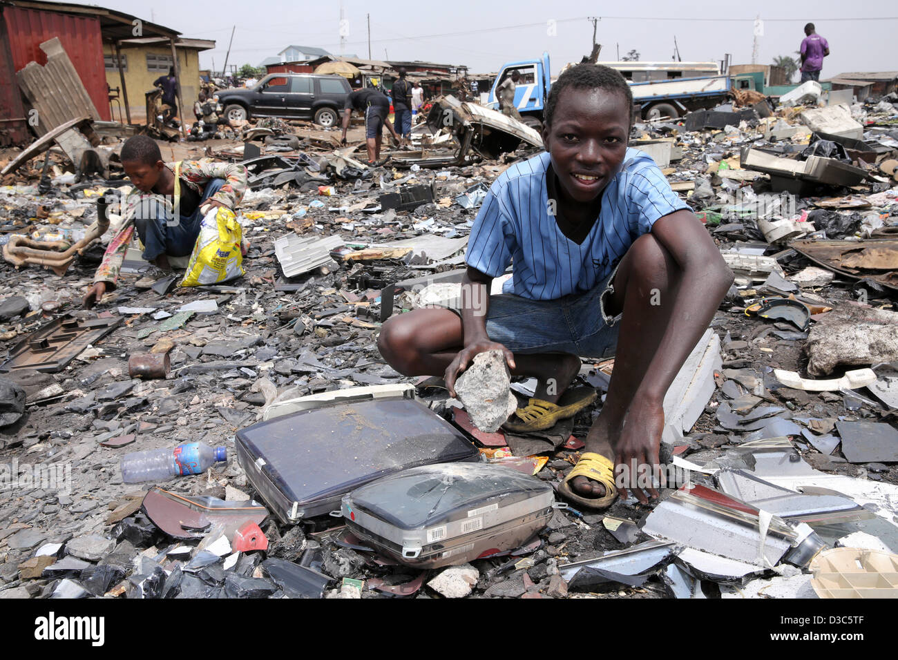 Adolescents démantèlement d'ordinateurs et autres appareils électroniques pour récupérer Photo Stock
