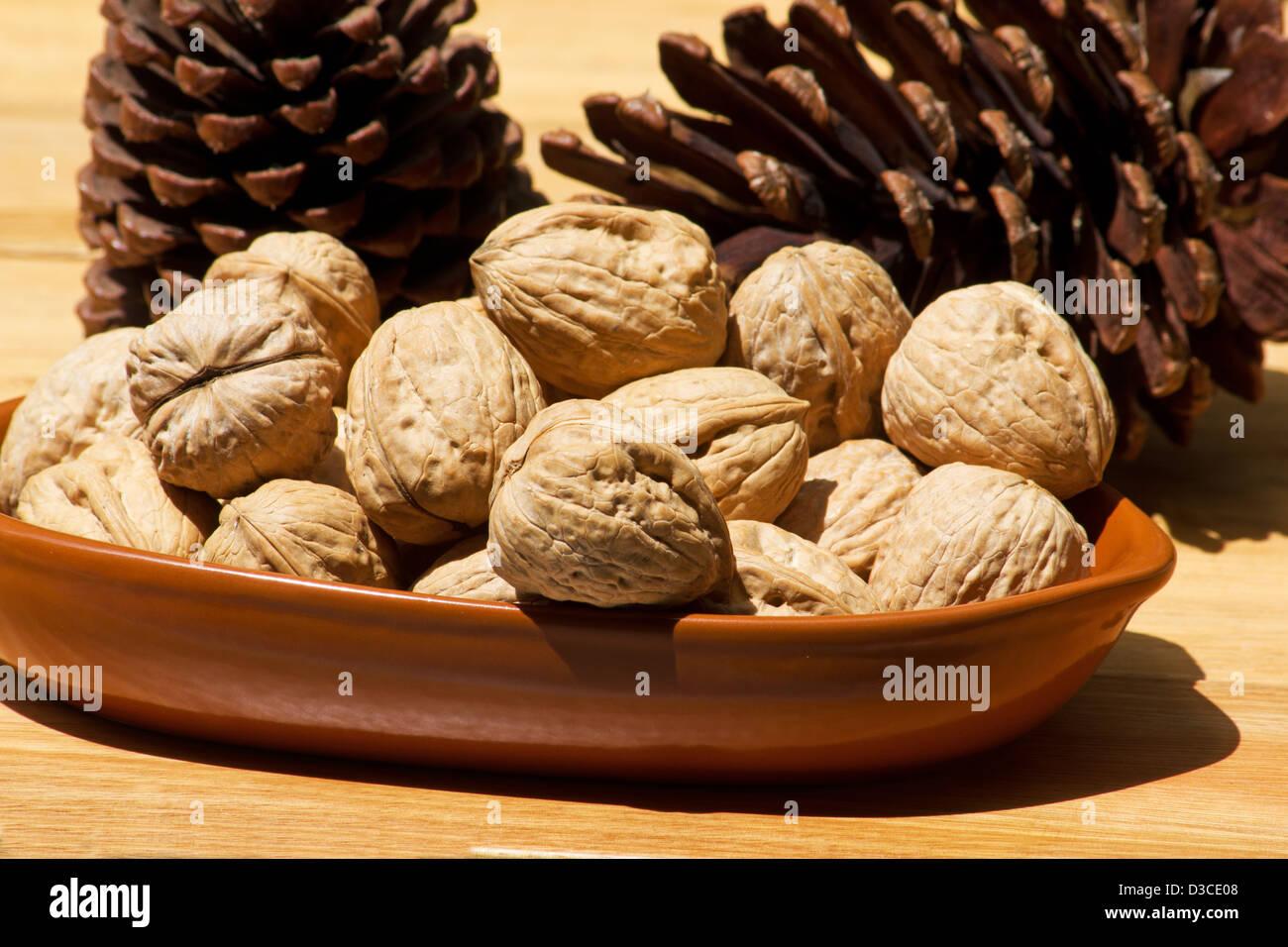 Close-up de noix dans un bol en céramique d'une pomme de pin Photo Stock