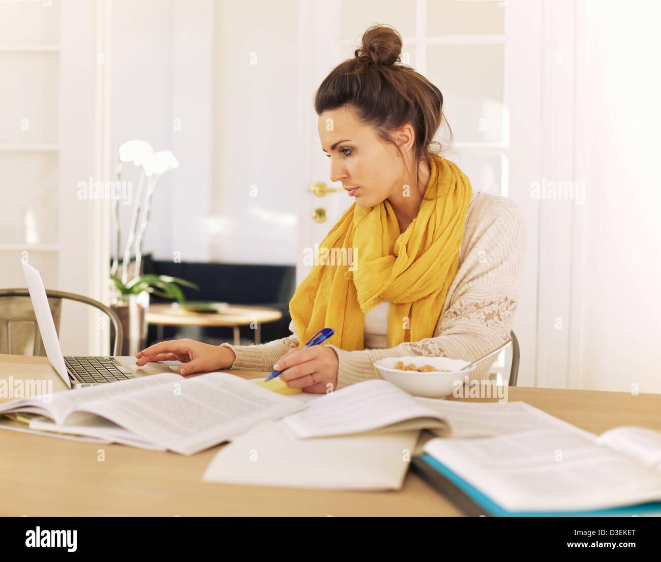 Young university student using laptop and books à l'étude à la maison Photo Stock
