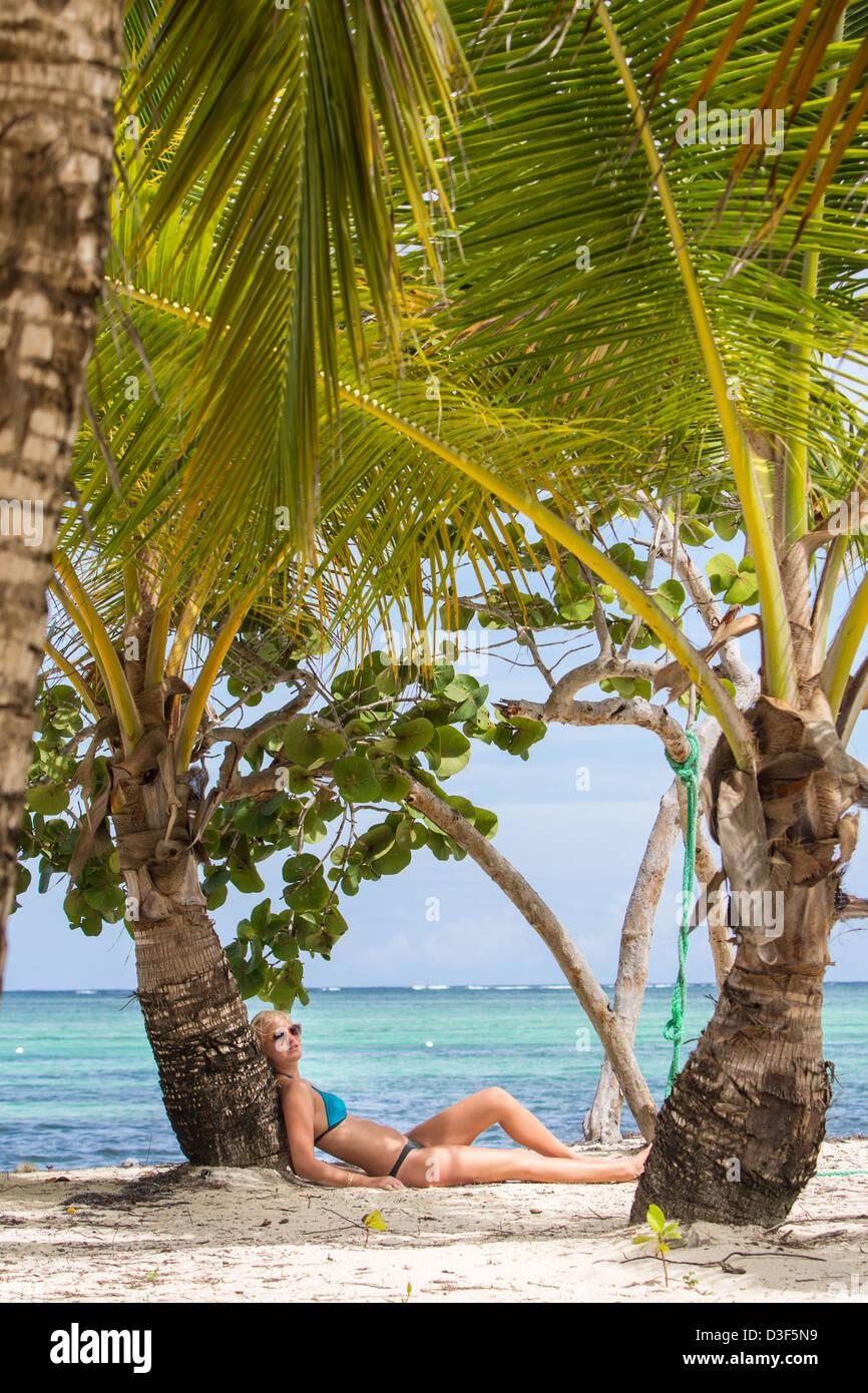 Une fille en maillot est assis au milieu des palmiers Photo Stock