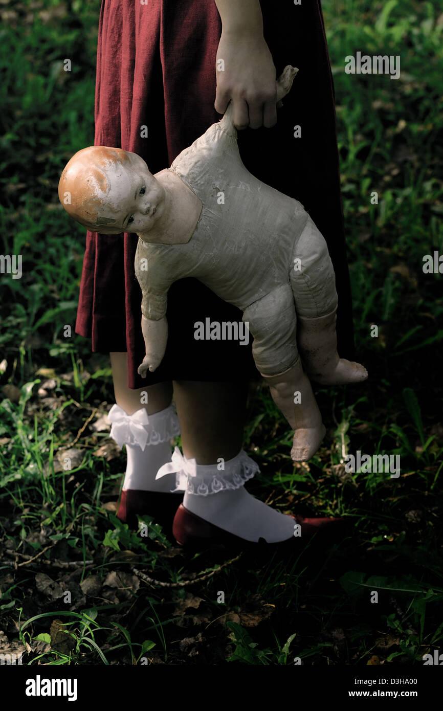 Une femme dans une robe rouge avec une vieille poupée Photo Stock