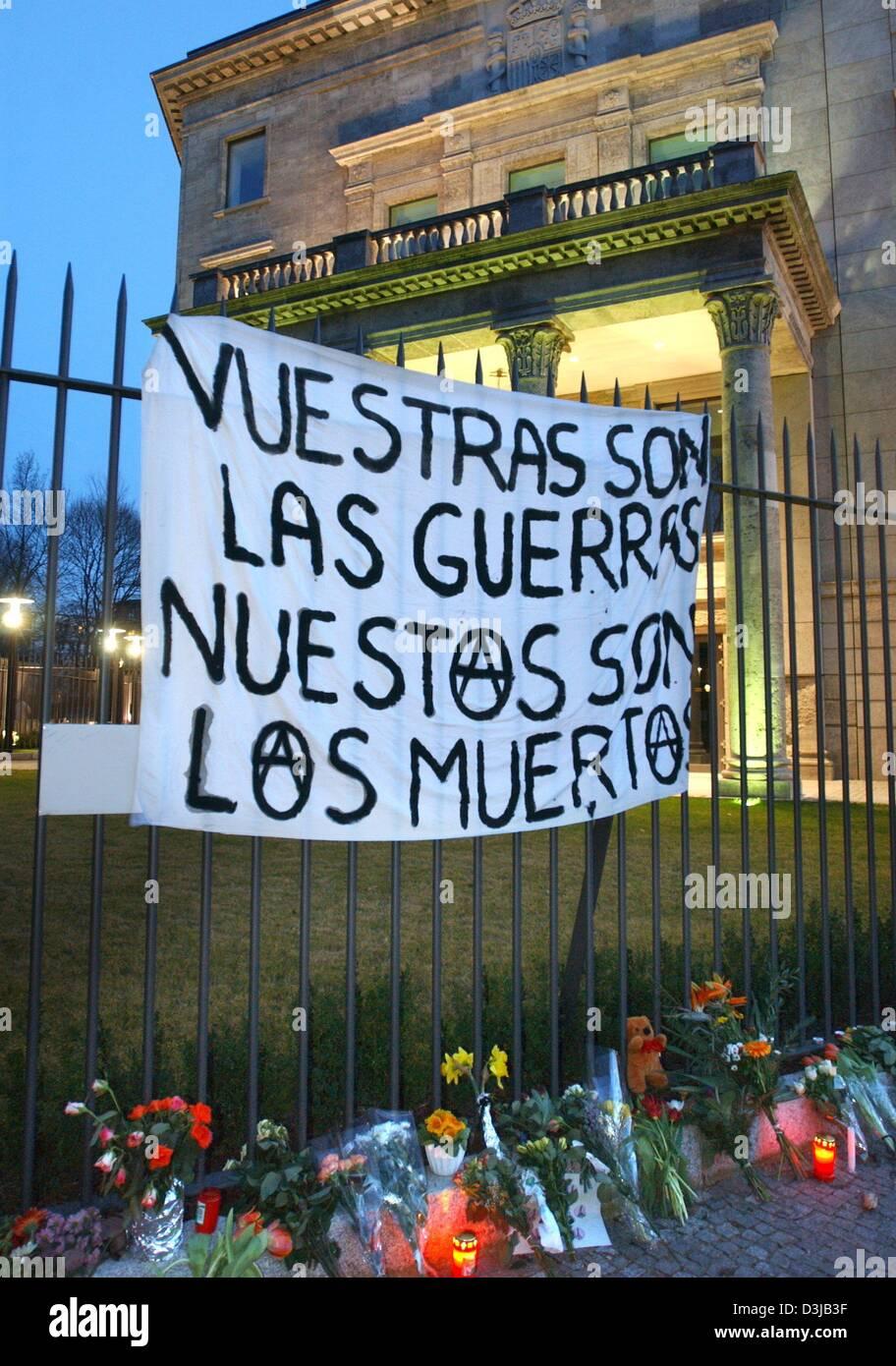 """(Afp) - Une bannière est suspendu au-dessus des bouquets de fleurs et de bougies attaché à une clôture entourant l'ambassade d'Espagne à Berlin, 14 mars 2004. La bannière indique 'Vuestras las Guerras, nuestros fils fils los muertos"""" (votre guerre et nos morts). Environ 30 personnes se sont réunies pour un rassemblement pour protester contre la politique du gouvernement espagnol. 200 personnes sont mortes et plus de 1 200 ont été blessés dans un Banque D'Images"""