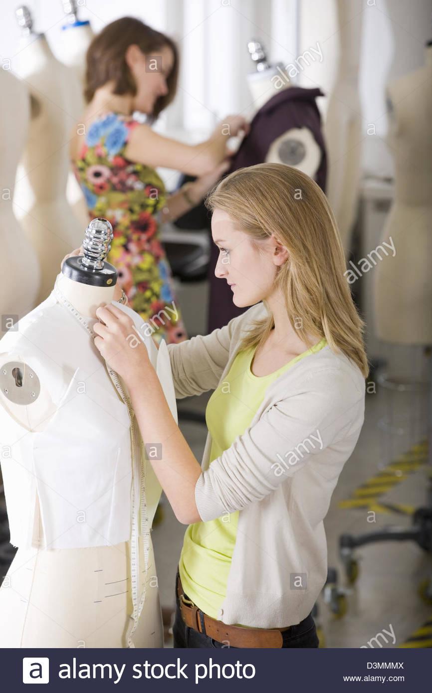 Fashion design student working on vêtement sur mannequin Photo Stock