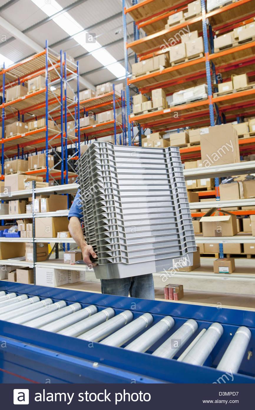 Worker carrying pile de bacs en entrepôt de distribution Photo Stock