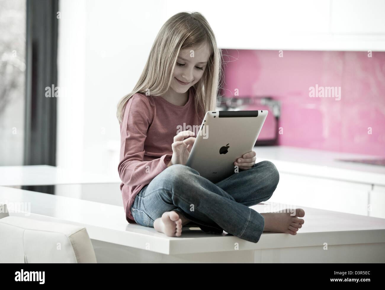 Jeune fille jouant sur un Apple iPad tablet computer Photo Stock