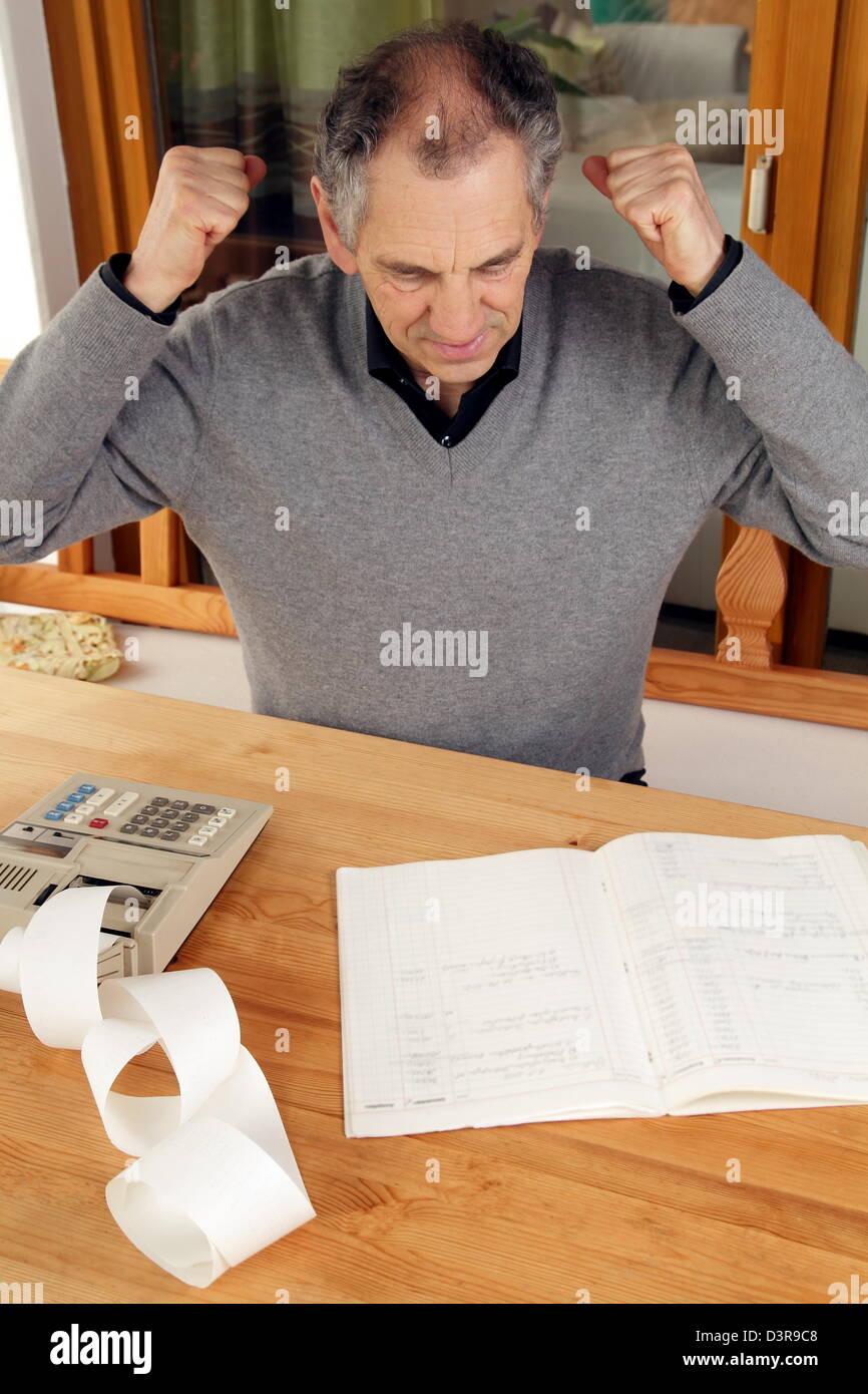 Vieil homme avec la calculatrice et livret Photo Stock
