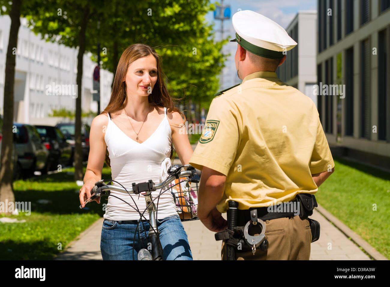 Police - jeune femme à bicyclette avec un policier dans le contrôle du trafic aérien Photo Stock