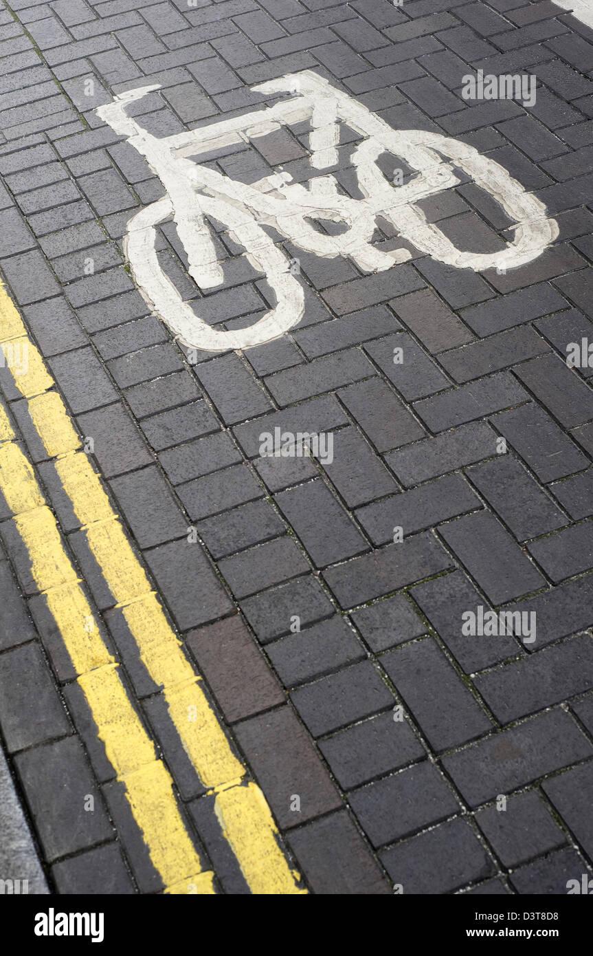 Voie cyclable désignée et double symbole lignes jaunes le marquage routier, peinte sur une rue pavée Photo Stock