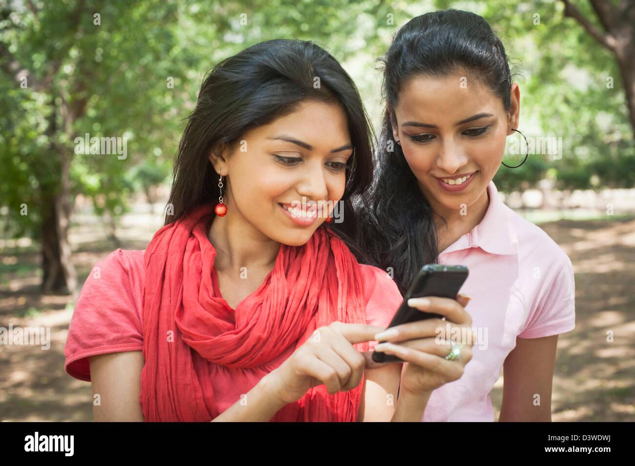 Les amis la messagerie texte sur un téléphone mobile, Lodi Gardens, New Delhi, Delhi, Inde Photo Stock