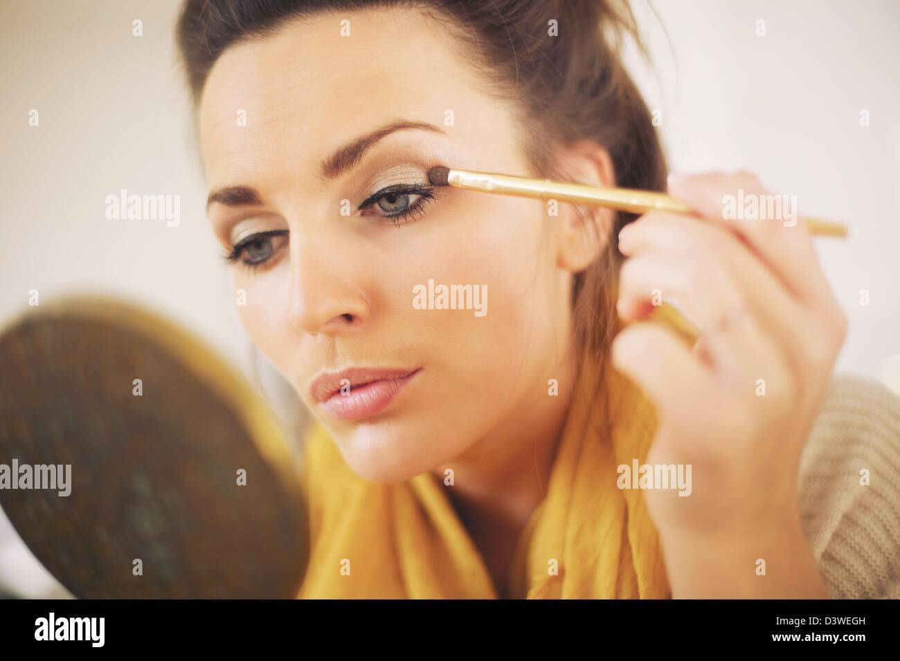 Jolie femme appliquant le maquillage tout en regardant le miroir Photo Stock