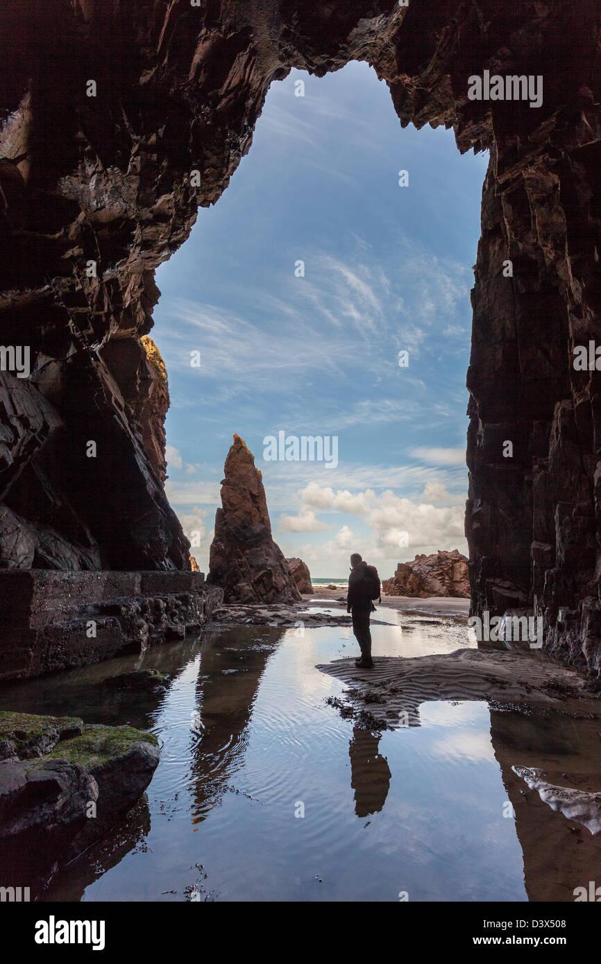 Rocher de l'aiguille avec personne debout dans Plemont Grotte, Jersey, Channel Islands, Royaume-Uni Photo Stock