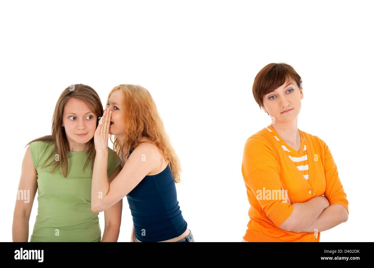 Deux filles whispering secrets à l'autre, et leur ami, vexé et rejeté Photo Stock