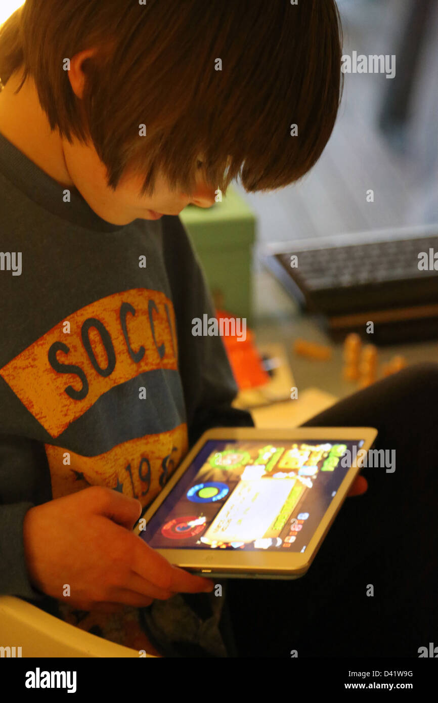 Jeu de garçon sur iPad Mini en Angleterre Photo Stock