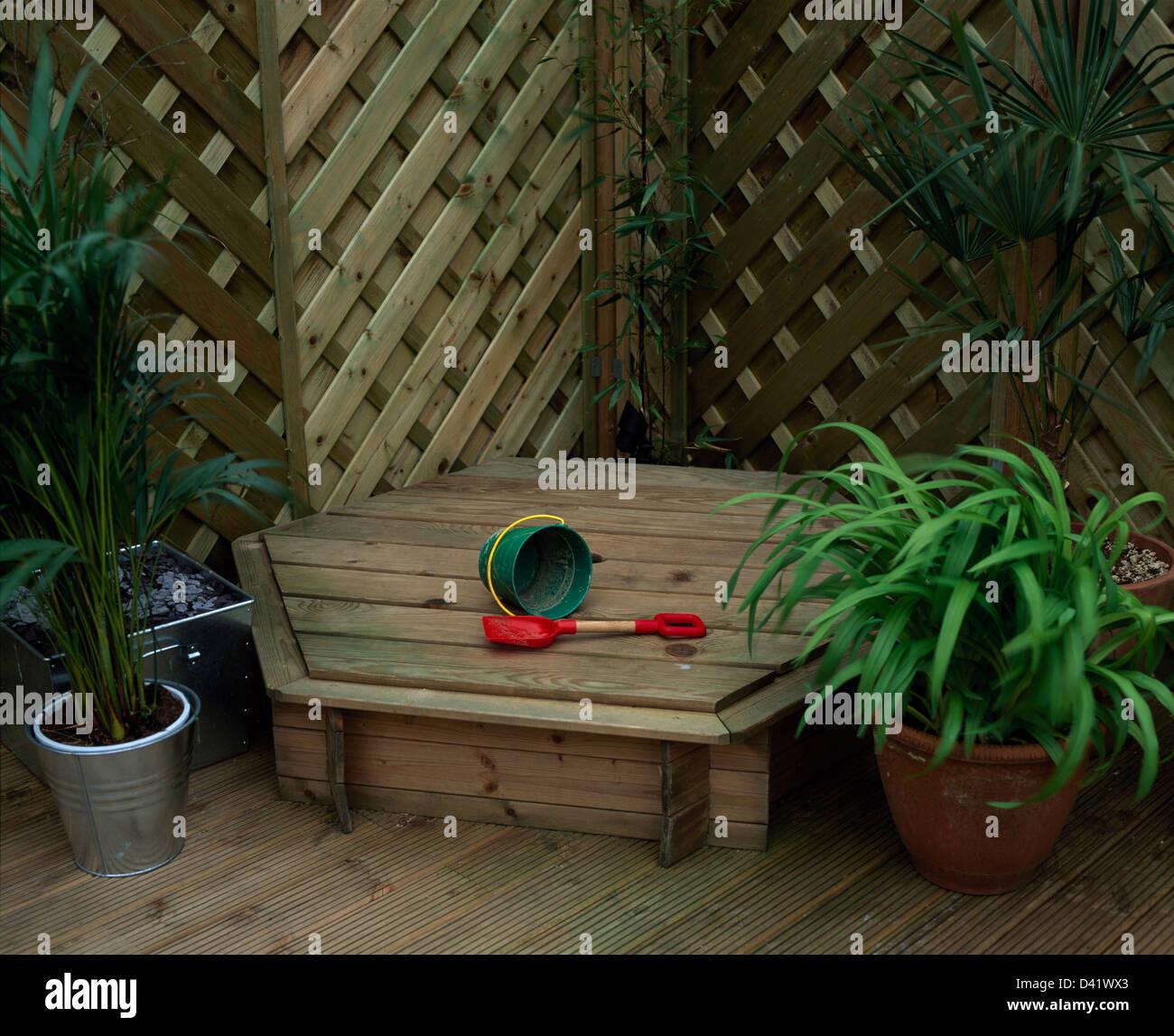plantes en pots de chaque côté du bac à sable avec couvercle en bois