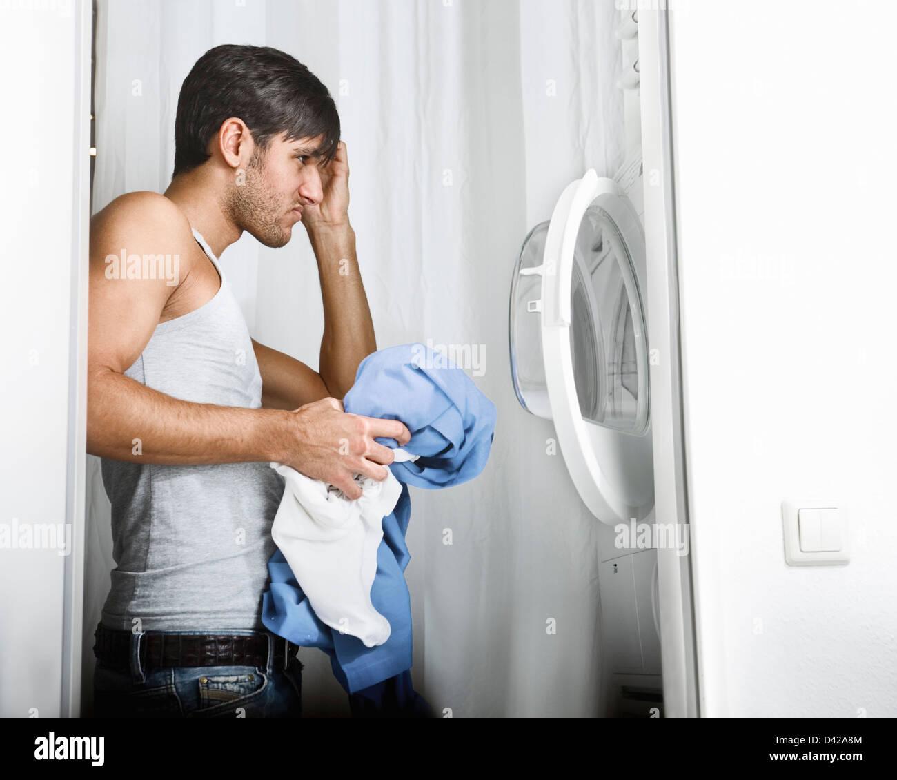 L'homme ayant des problèmes d'utiliser la machine à laver sur Jour de lessive Photo Stock