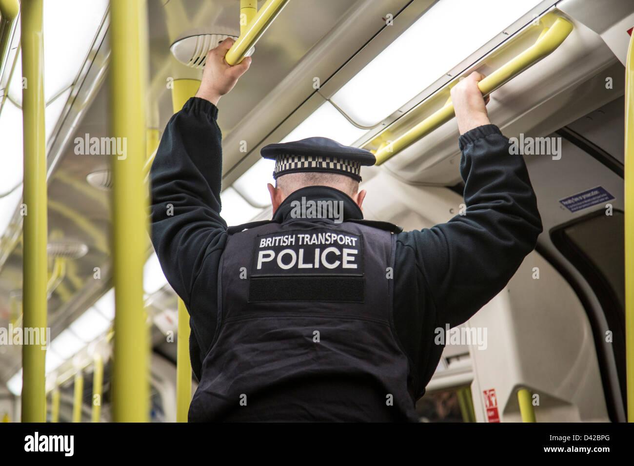 Agent de police britannique des transports sur train de tube underground Photo Stock