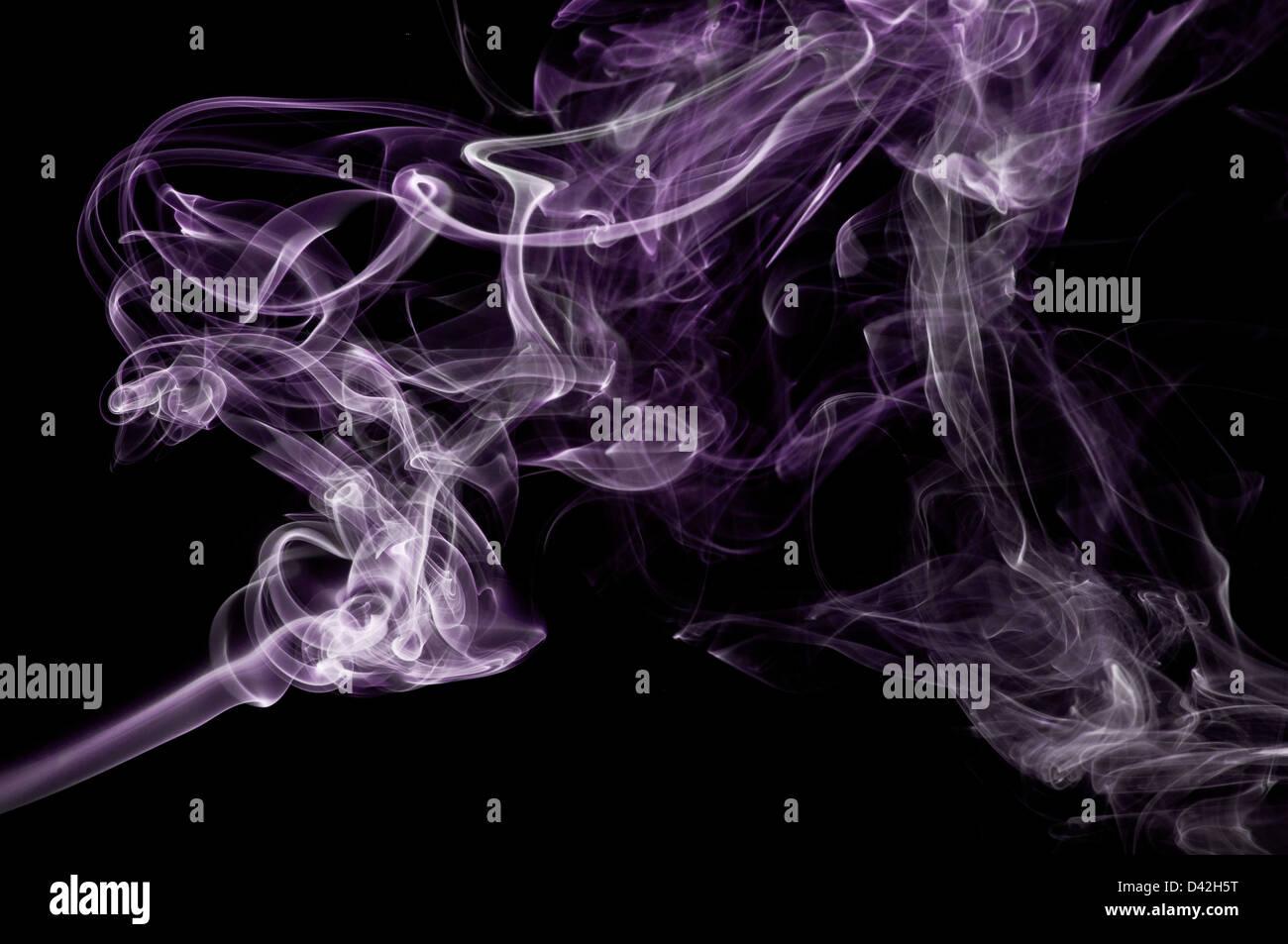 Une image abstraite de fumée mauve sur un fond noir. Banque D'Images